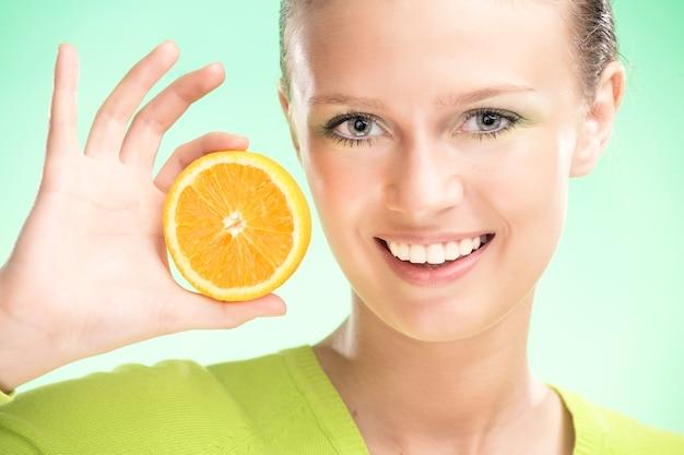 Jonge schoonheidsvrouw met sinaasappel op groene achtergrond