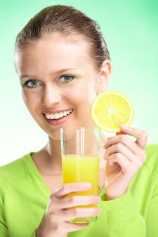 Jonge schoonheidsvrouw met vruchtensappen op groene achtergrond