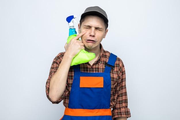 Jonge schoonmaakster draagt uniform en pet met vod met schoonmaakmiddel geïsoleerd op een witte muur