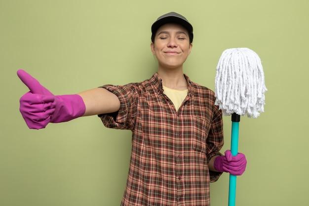 Jonge schoonmaakster in geruit hemd en pet in rubberen handschoenen met dweil blij en vrolijk glimlachend met duimen omhoog staande over groene muur