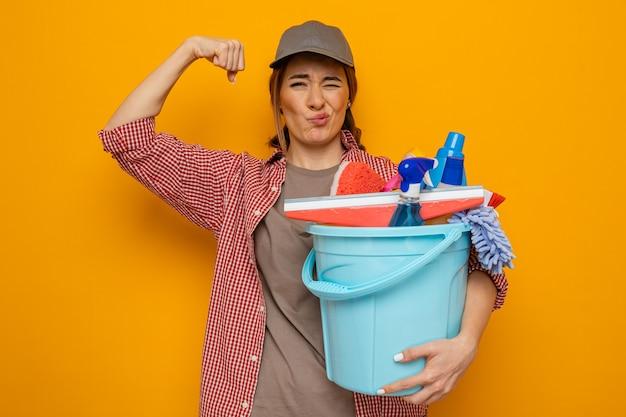 Jonge schoonmaakster in geruit hemd en pet met emmer met schoonmaakgereedschap kijkend naar camera met zelfverzekerde uitdrukking blij en positief opheffende vuist als een winnaar die over oranje achtergrond staat