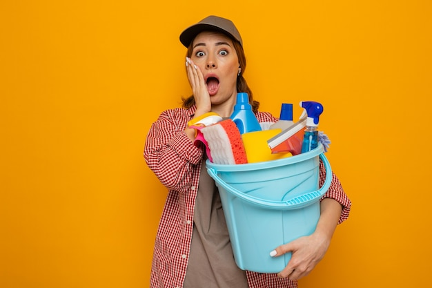 Jonge schoonmaakster in geruit hemd en pet met emmer met schoonmaakhulpmiddelen die verbaasd en verrast zijn mond met de hand bedekken