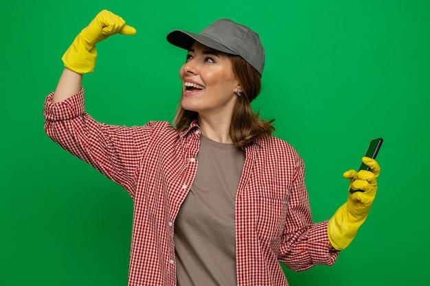 Jonge schoonmaakster in geruit hemd en pet met rubberen handschoenen, blij en opgewonden met smartphone die vuist opheft, een winnaar