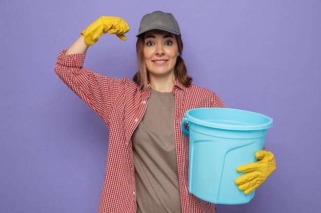 Jonge schoonmaakster in geruit hemd en pet met rubberen handschoenen die een emmer vasthoudt en glimlachend de vuist opheft als een winnaar