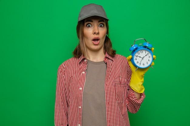 Jonge schoonmaakster in geruit hemd en pet met rubberen handschoenen die een wekker vasthoudt en er bezorgd uitziet