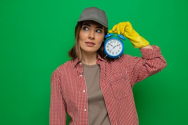 Jonge schoonmaakster in geruit hemd en pet met rubberen handschoenen die een wekker vasthoudt en verward opzij kijkt