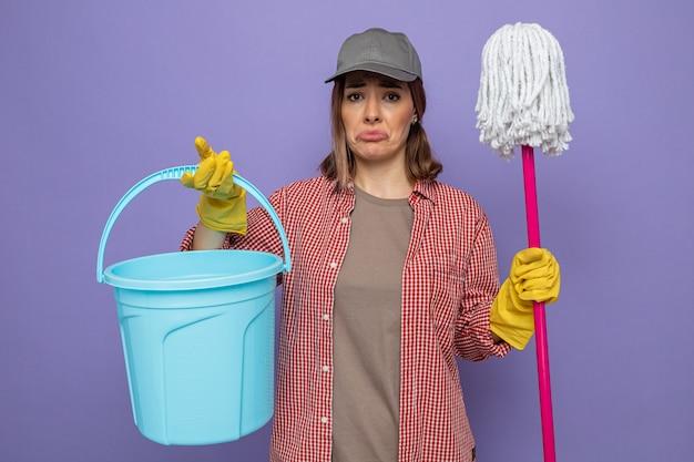 Jonge schoonmaakster in geruit hemd en pet met rubberen handschoenen die emmer en dweil vasthoudt en kijkt met een droevige uitdrukking