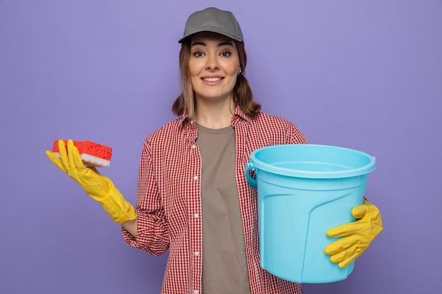 Jonge schoonmaakster in geruit hemd en pet met rubberen handschoenen die emmer en spons vasthoudt en naar camera kijkt glimlachend zelfverzekerd over paarse achtergrond