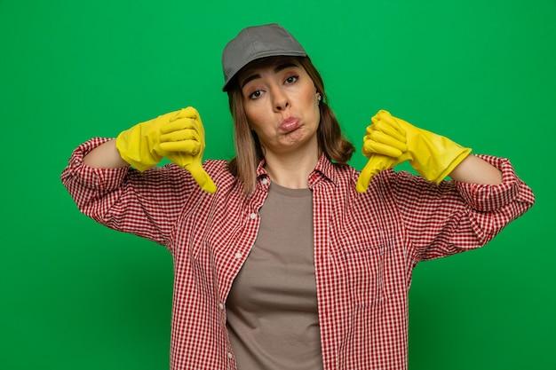 Jonge schoonmaakster in geruit hemd en pet met rubberen handschoenen die naar de camera kijkt, ontevreden met duimen naar beneden staande over groene achtergrond