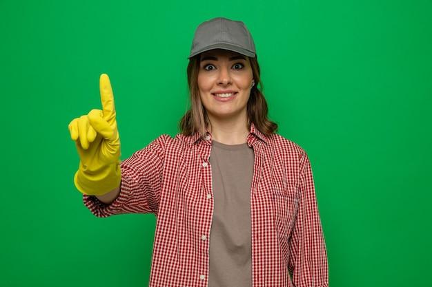 Jonge schoonmaakster in geruit hemd en pet met rubberen handschoenen kijkend naar camera blij en verrast met wijsvinger met nieuw idee over groene achtergrond