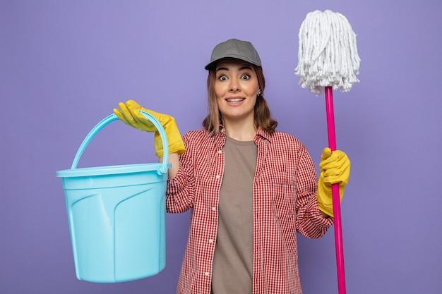 Jonge schoonmaakster in geruit hemd en pet met rubberen handschoenen met emmer en dweil kijkend naar camera blij en verrast glimlachend vrolijk staande over paarse achtergrond