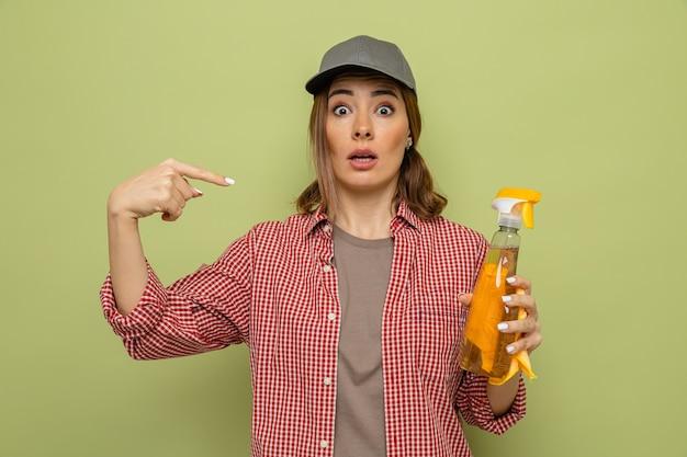 Jonge schoonmaakster in geruit hemd en pet met vod en reinigingsspray wijzend met wijsvinger naar spray die er verbaasd uitziet