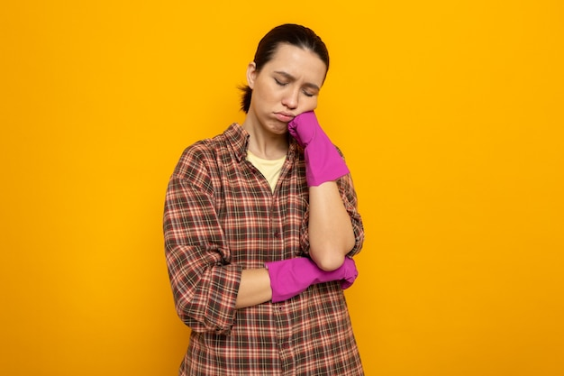 Jonge schoonmaakster in geruit hemd in rubberen handschoenen die er moe en verveeld uitziet, leunend op haar vuist die op oranje staat