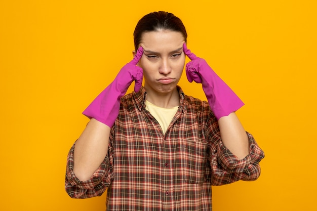 Jonge schoonmaakster in geruit hemd in rubberen handschoenen die haar slapen aanraakt en er onwel moe en uitgeput uitziet terwijl ze over een oranje muur staat