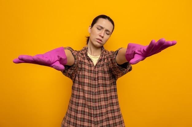 Jonge schoonmaakster in geruit hemd in rubberen handschoenen die probeert te lopen met gesloten ogen en hand in hand voor zichzelf staande op oranje