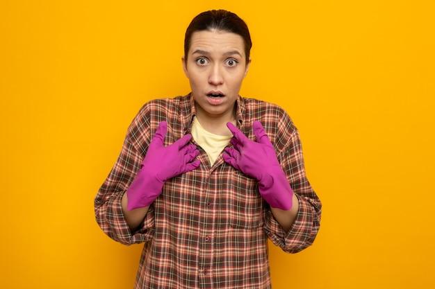 Jonge schoonmaakster in geruit hemd in rubberen handschoenen kijkend naar de voorkant, verbaasd wijzend naar zichzelf terwijl ze over de oranje muur staat