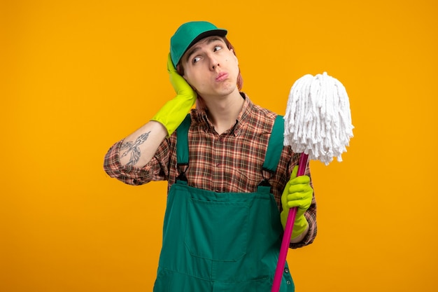 Jonge schoonmaakster in geruit hemd jumpsuit en pet met rubberen handschoenen die een dweil vasthoudt en er verbaasd uitziet