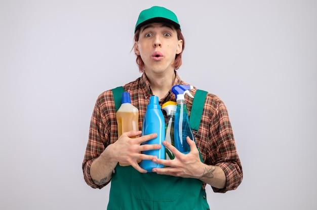 Jonge schoonmaakster in geruit hemd jumpsuit en pet met schoonmaakspullen