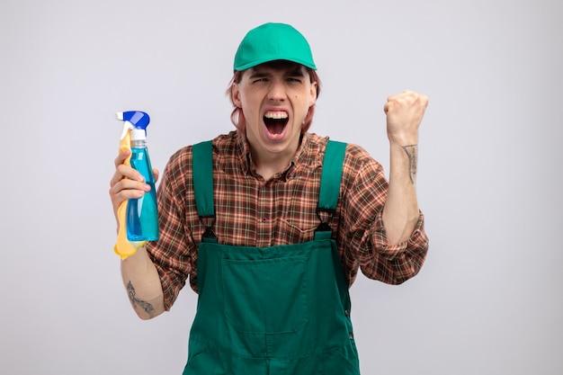 Jonge schoonmaakster in geruit hemd jumpsuit en pet met vod en schoonmaakspray die schreeuwend kijkt met een agressieve uitdrukking die de vuist opheft