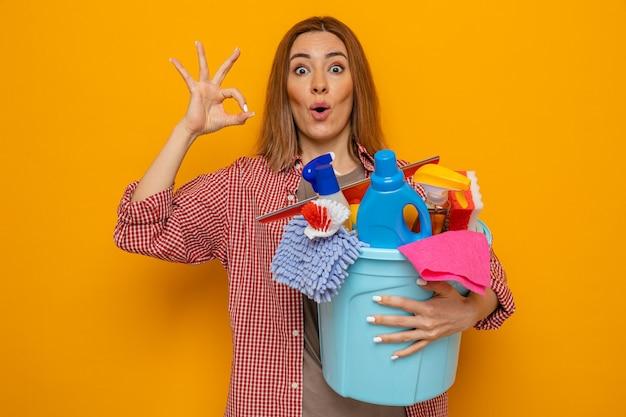 Jonge schoonmaakster in geruit hemd met emmer met schoonmaakgereedschap die verbaasd en verrast kijkt terwijl ze een goed teken doet