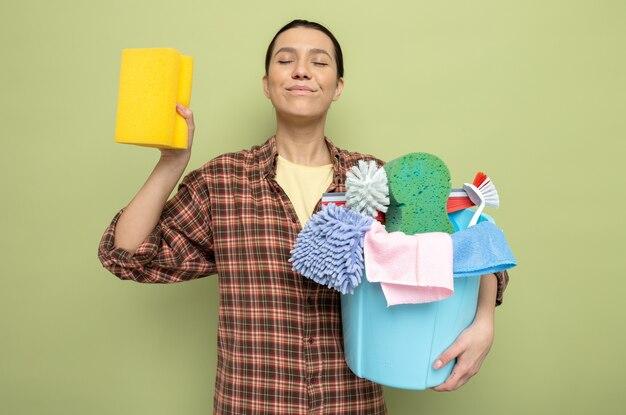 Jonge schoonmaakster in geruit hemd met emmer met schoonmaakgereedschap en spons blij en positief glimlachend over groene muur