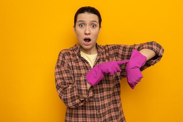 Jonge schoonmaakster in geruit overhemd in rubberen handschoenen verward wijzend op haar arm en herinnert aan de tijd die over de oranje muur staat