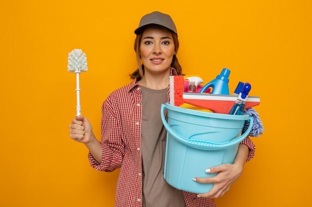 Jonge schoonmaakster in plaidoverhemd en glb die emmer met schoonmakende hulpmiddelen en schoonmaakborstel houden die vrolijk gelukkig en positief klaar glimlachen