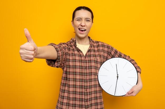 Jonge schoonmaakster in vrijetijdskleding die de klok vasthoudt en naar de voorkant kijkt, vrolijk en vrolijk met duimen die over de oranje muur staan