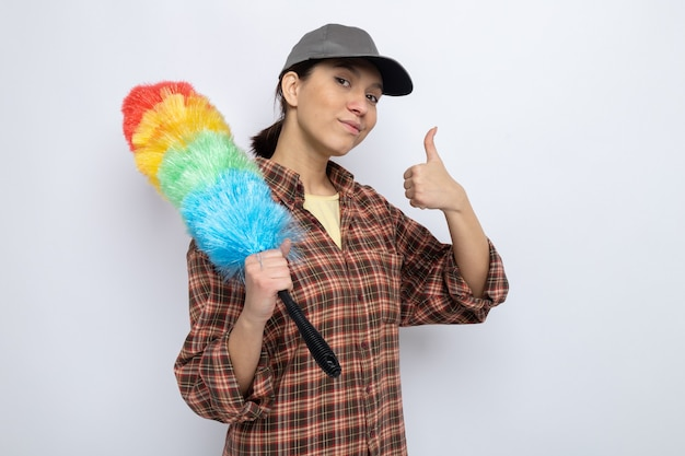 Jonge schoonmaakster in vrijetijdskleding en pet met kleurrijke stofdoekborstel