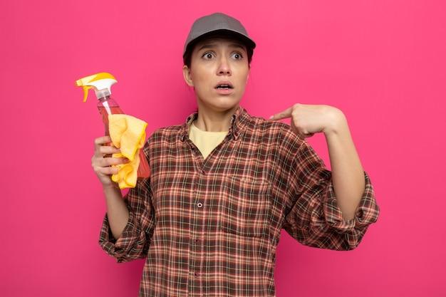 Jonge schoonmaakster in vrijetijdskleding en pet met vod en reinigingsspray die verbaasd en verward kijkt terwijl ze zelf over roze muur staat
