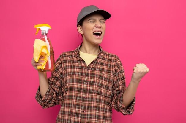 Jonge schoonmaakster in vrijetijdskleding en pet met vod en schoonmaakspray blij en opgewonden gebalde vuist over roze muur