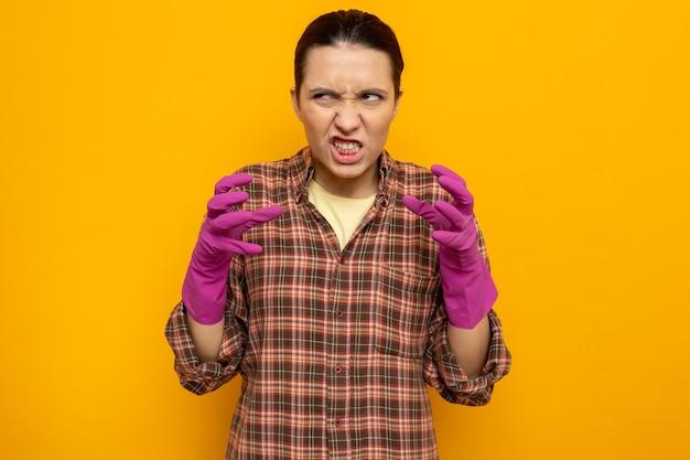 Jonge schoonmaakster in vrijetijdskleding in rubberen handschoenen die een wrange mond boos en gefrustreerd maakt met opgeheven armen die op oranje staan