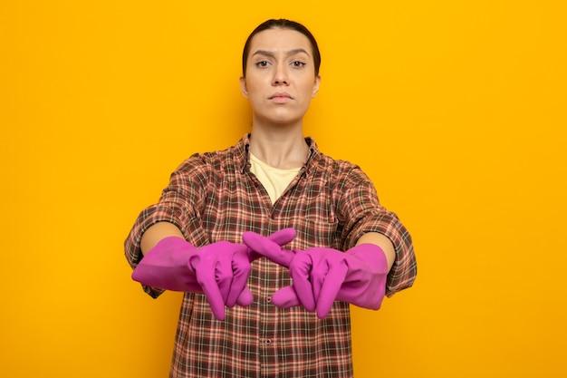 Jonge schoonmaakster in vrijetijdskleding in rubberen handschoenen die met een serieus gezicht kijkt en een verdedigingsgebaar maakt terwijl ze de wijsvinger kruist