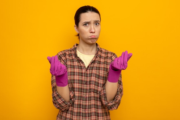 Jonge schoonmaakster in vrijetijdskleding in rubberen handschoenen ontstemd blazende wangen wrijven vingers over oranje muur