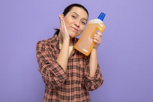 Jonge schoonmaakster in vrijetijdskleding met een fles schoonmaakbenodigdheden die blij en positief glimlacht over de paarse muur