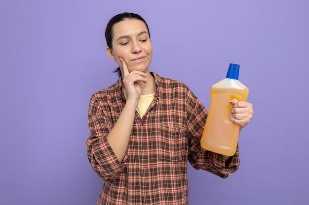 Jonge schoonmaakster in vrijetijdskleding met een fles schoonmaakspullen die ernaar kijkt met een peinzende uitdrukking op een paarse achtergrond