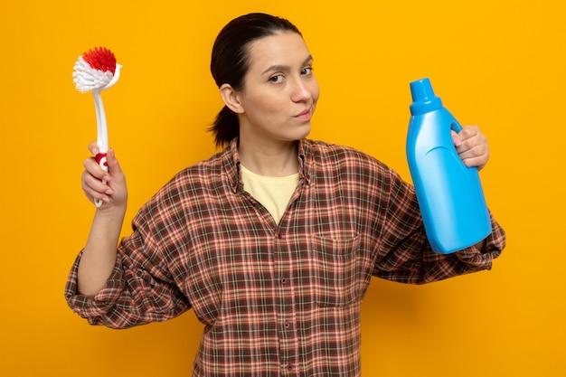 Jonge schoonmaakster in vrijetijdskleding met een schoonmaakborstel en een fles schoonmaakbenodigdheden die er met een serieus gezicht uitziet