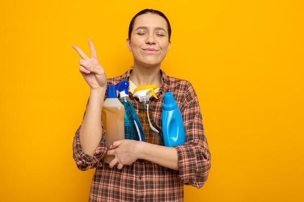 Jonge schoonmaakster in vrijetijdskleding met schoonmaakspullen blij en vrolijk met een v-teken dat over een oranje muur staat