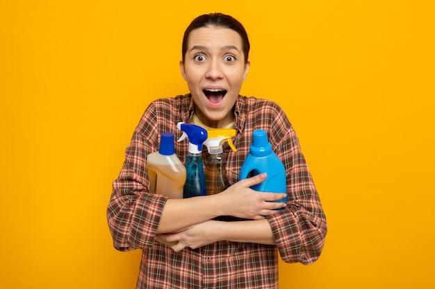 Jonge schoonmaakster in vrijetijdskleding met schoonmaakspullen die blij en opgewonden naar voren kijkt en over oranje muur staat