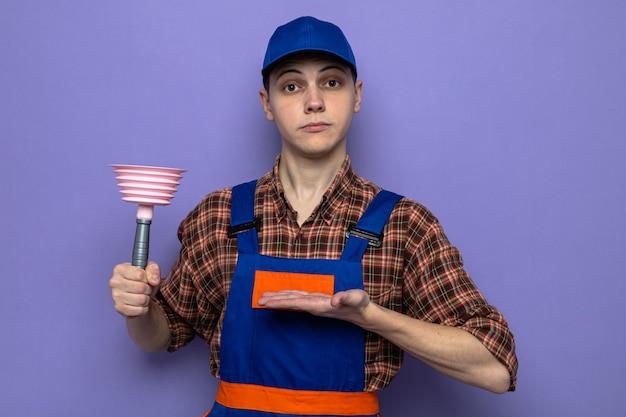 Jonge schoonmaakster met uniform en dop die vasthoudt en wijst met handplunjer geïsoleerd op blauwe muur
