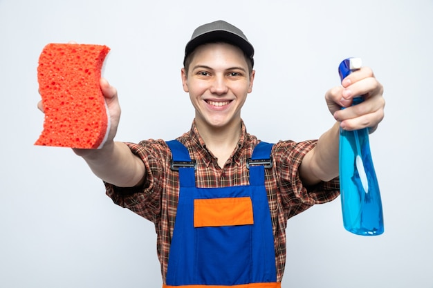 Jonge schoonmaakster met uniform en pet die een spons met reinigingsmiddel naar de camera steekt die op een witte muur is geïsoleerd