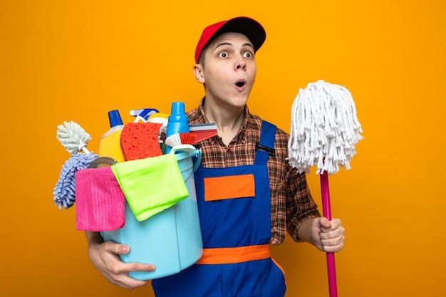 Jonge schoonmaakster met uniform en pet met emmer schoonmaakgereedschap met dweil geïsoleerd op oranje muur