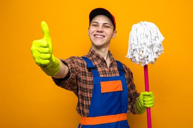 Jonge schoonmaakster met uniform en pet met handschoenen die een dweil op een oranje muur houden