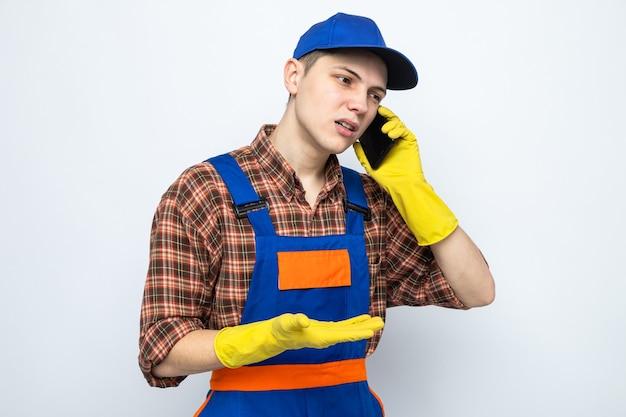 Jonge schoonmaakster met uniform en pet met handschoenen die handen spreiden, spreekt op telefoon geïsoleerd op een witte muur