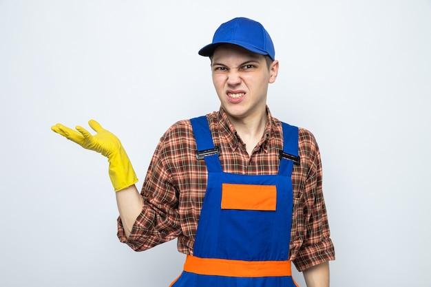 Jonge schoonmaakster met uniform en pet met handschoenen geïsoleerd op een witte muur