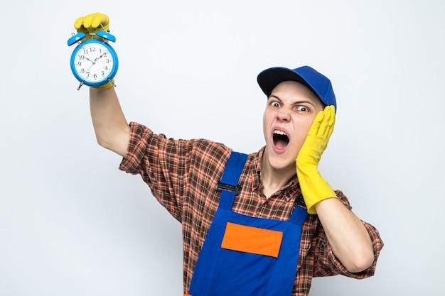 Jonge schoonmaakster met uniform en pet met handschoenen met wekker geïsoleerd op een witte muur