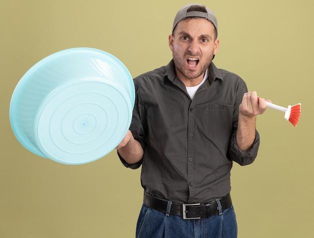 Jonge schoonmakende mens die vrijetijdskleding en glb draagt die bekken en schoonmaakborstel schreeuwen met geïrriteerde uitdrukking die zich over groene muur bevindt