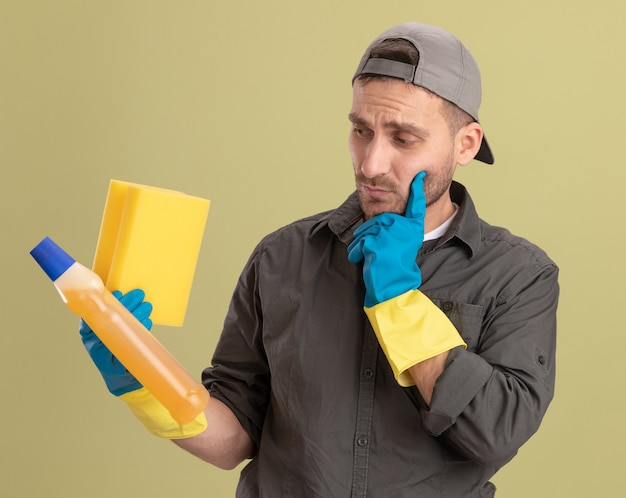 Jonge schoonmakende mens die vrijetijdskleding en glb in rubberhandschoenen draagt die fles met schoonmakende levering en spons houdt die het met peinzende uitdrukking bekijkt die zich over groene muur bevindt