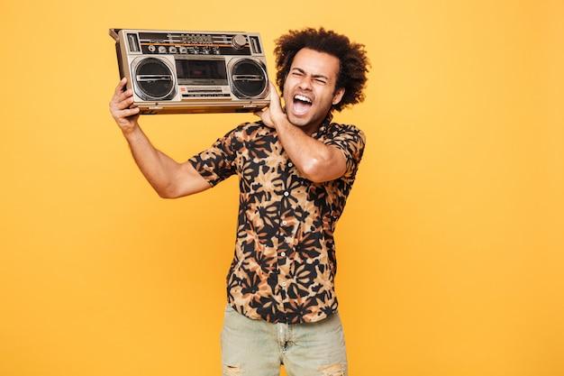Jonge schreeuwende afrikaanse mens die zich met bandrecorder bevindt