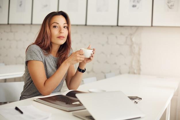 Jonge schrijver die het drinken van koffie ontspant die door tijdschrift in een lichte studioruimte bladert.
